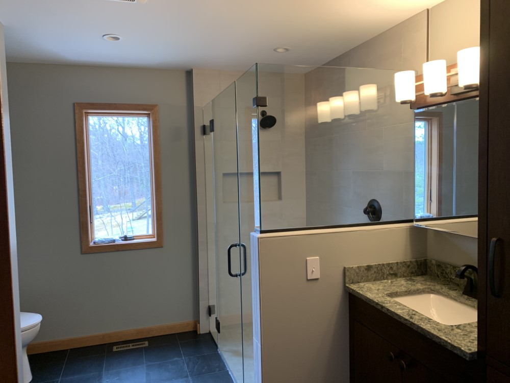 Bathroom with glass door shower slate floor with a window